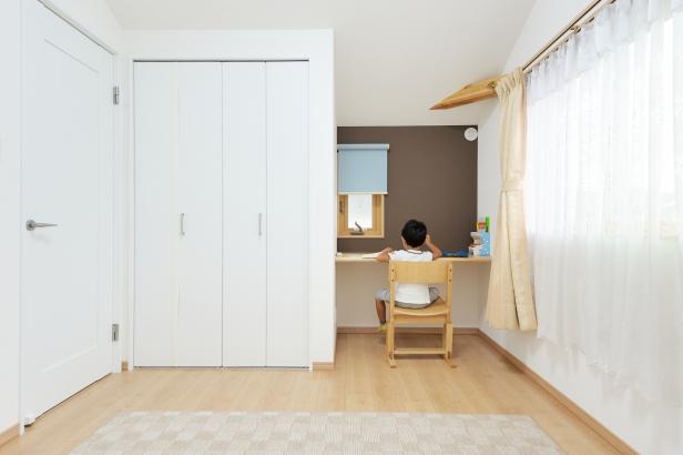 造付のカウンター机と画鋲が押せる壁を設けた子ども部屋