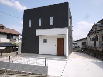 外観は白と黒のモノトーンのすっきりとしたデザインが目を惹くお家。 調和のとれたフォルムの外観デザイン。開放感あふれる吹抜けから明るい光がリビングに差し込みます。キッチンを家の中心に配置し家事動線を考えたプラン。