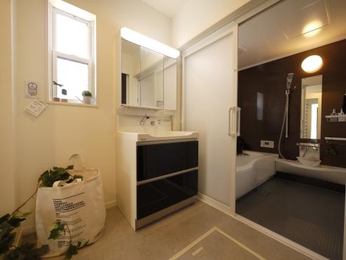 【1階:洗面所】 収納棚を設置し、洗面所の限られたスペースをすっきりに。